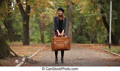 Redhead girl with suitcase at outdoor