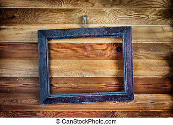 Old vintage frame hanging on the wooden wall