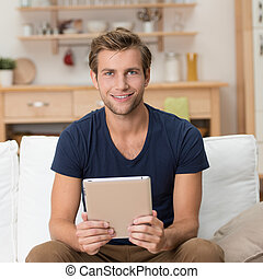 Casual young man holding a tablet-pc - Casual young man...