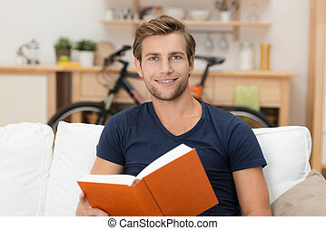 Young man reading a book - Handsome young man sitting on a...
