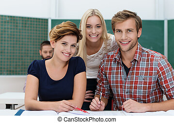 Smiling university students, an attractive young man and two...