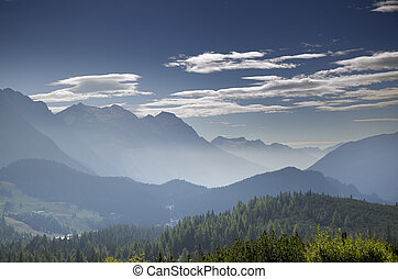 Panoramic view over mountain with fog and blue sky and...