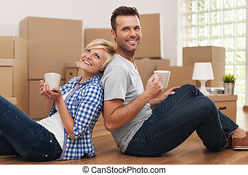Attractive couple sitting on the floor at home with coffee...