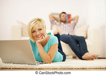 Attractive blonde woman using computer on the carpet