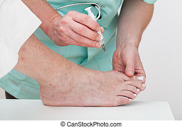 Foot injection - A patient having an injection done by a...