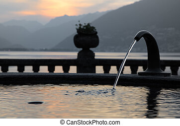 Fountain - Water fountain in sunset with a lake and mountain