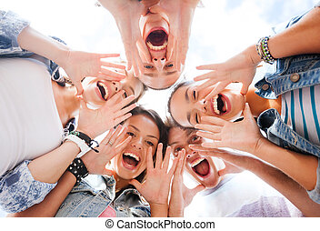 group of teenagers looking down and screaming - summer...