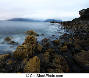 Coastal landscape by a rainy and windy day at Elgol port in...