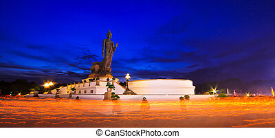 Buddha statue candle lit in lent day thailand