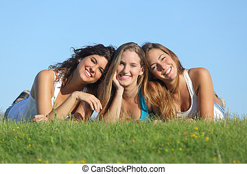 Portrait of a group of three happy teenager girls smiling...