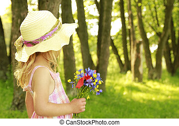 beautiful little girl with a bouquet of flowers in nature -...