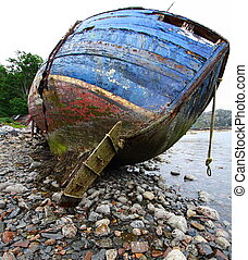 wreck wooden boat on a desolate beach in scotland