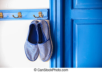 Blue women's slippers in Greek style of house on the...