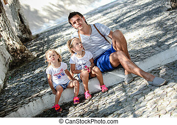 Young father and cute daughters sitting on street in old...