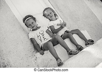 Little cute sisters sitting near old house in Greek village of Emporio, Santorini