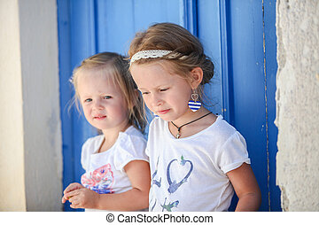 Portrait of Little smiling girls sitting near old blue door...