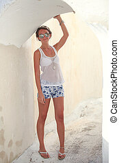 Young woman walking in narrow streets of Emporio village on the island Santorini,Greece