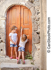 Little cute sisters near old door in Greek village of Emporio, Santorini