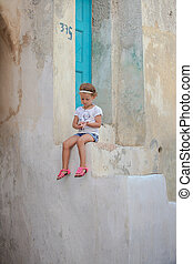 Adorable little girl sitting on the steps of old house in...
