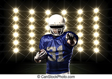 Football Player with a Blue uniform in front of lights
