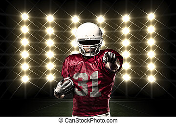 Football Player with a Red uniform in front of lights.