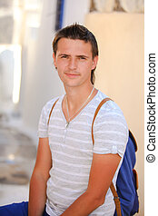 Portrait of young man sitting at street in Greek village, Emporio, Santorini