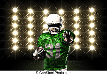Football Player with a green uniform in front of lights.