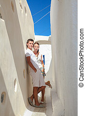 Young couple walking in old greek village on Santorini island, Greece
