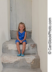 Cute little girl sitting on doorstep of old house in Emporio village, Santorini, Greece