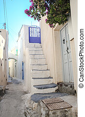 Narrow street and white houses in Emporio village of Santorini archipelago