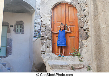 Little cute girl in medieval village of Emporio at Santorini island, Greece