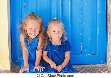 Portrait of Little adorable girls sitting near old blue door...