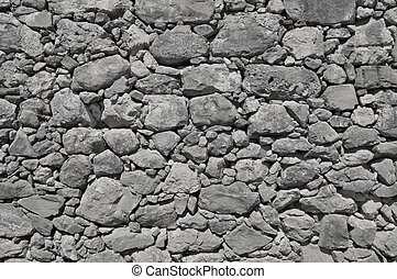 dark grey old wall made of big and little stones - dark grey...