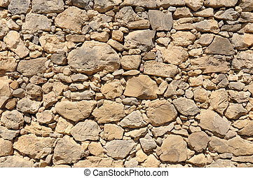 yellow old wall made of big and little stones - yellow old...