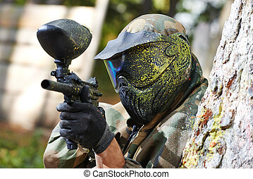 paintball player in protective uniform and mask aiming gun...