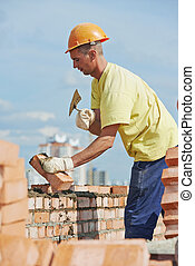 construction mason worker bricklayer installing red brick...