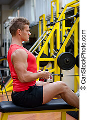 Attractive young man working out on gym equipment