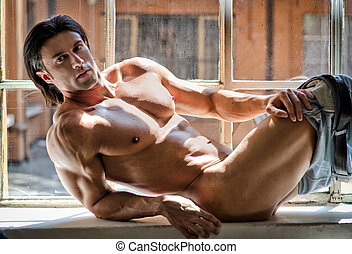 Half naked attractive young man with muscular body - Half...