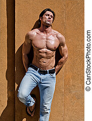 Handsome young man shirtless with jeans against a wall, eyes...