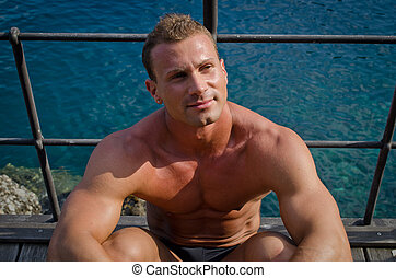 Handsome young muscle man sitting with sea behind -...