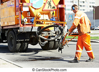 Asphalt patching roadworks - Road worker at asphalt roadway...