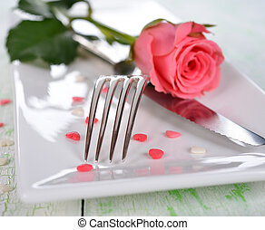 Cutlery and rose on a white table