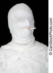 Mummy with cigarette on the black background