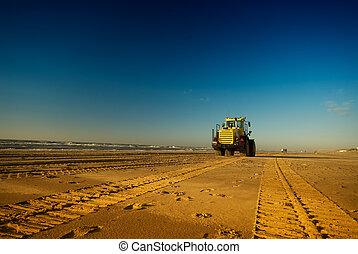 bulldozer on the beach - tracks on the beach with a...