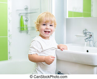 Happy kid washing in bathroom