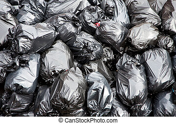 Garbage bags - A pile of black garbage bags with tons of...