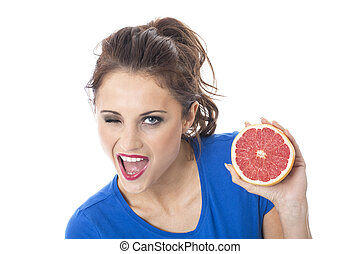 Model Released. Attractive Young Woman Holding Pink Grapefruit