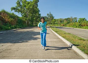 Young Indian jogger running and exercising on a wide empty...