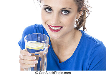 Model Released. Attractive Young Woman Drinking a Glass of...