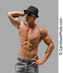 Handsome young man naked, wearing only jeans and hat in cool...